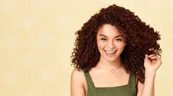 Woman smiling and loving her natural tight curls cared for by Suave® Hair products