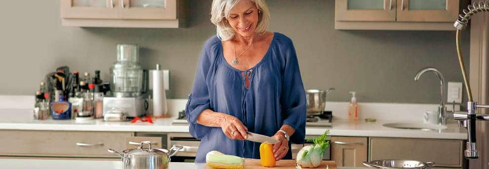 Older woman smiling while chopping vegetables